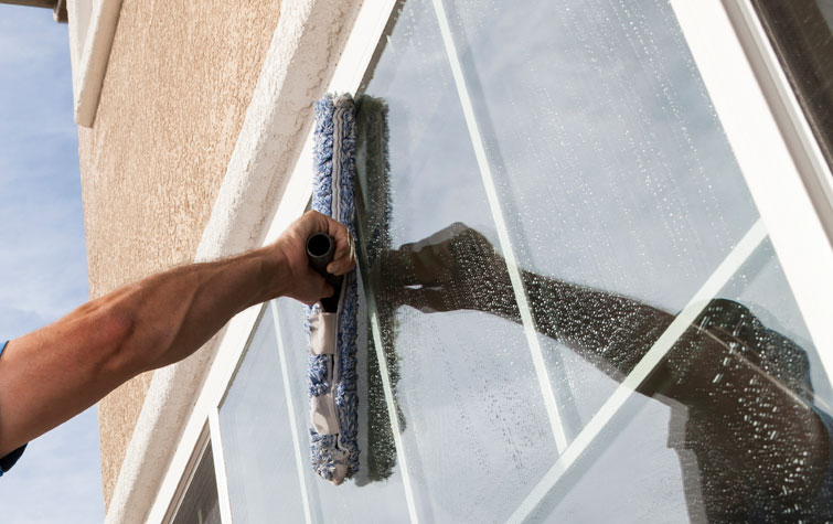 Squeaky-Kleen-cleaning-a-window-in-Bentonville-AR
